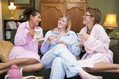 image of housecoat  - Three woman in night clothes sitting at home drinking tea - JPG