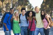 stock photo of ethnic group  - Six people outdoors standing arm in arm together  - JPG