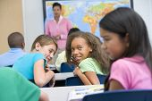 stock photo of tweenie  - Students in class bullying student with teacher in background  - JPG
