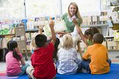 stock photo of hands up  - Students in class volunteering for teacher - JPG
