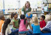 stock photo of student teacher  - Teacher in class showing students a globe - JPG