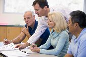 stock photo of only mature adults  - Adult students in class with teacher helping  - JPG