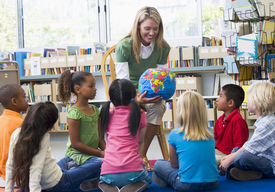 picture of student teacher  - Teacher in class showing students a globe - JPG