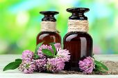 Medicine bottles with clover flowers on wooden table, outdoors