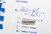 pic of pronunciation  - Mortgage cutout newspaper with equation for loan payments - JPG