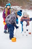 Two boys build wall of snow blocks, girl with plastic bucket stands little aside and looks at them