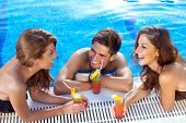 image of vivacious  - Good looking guy flirting with two women at the swimming pool drinking cocktails - JPG