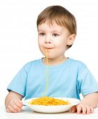 Little boy is sucking up a single spaghetti strand, isolated over white