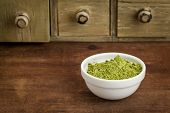 stock photo of moringa oleifera  - moringa leaf powder in a small bowl with a rustic drawer cabinet - JPG