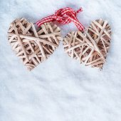 Two beautiful romantic vintage entwined beige flaxen hearts tied together with a ribbon on a white s