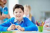stock photo of schoolboys  - Portrait of happy schoolboy at workplace looking at camera with his classmates on background - JPG