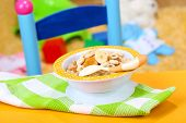 foto of porridge  - Bowl of porridge for baby and toys  on table - JPG
