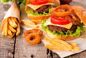 stock photo of fried onion  - Onion ringsfrench fries and cheeseburger on the wooden table - JPG