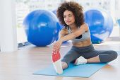 stock photo of slender legs  - Full length of a sporty young woman stretching hands to leg in fitness studio - JPG