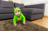 Baby creeping at home with dinosaur dressing