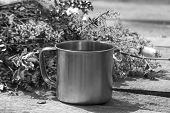 image of ferrous metal  - Tourist metal cup next to the flowers stands on a gray wooden table - JPG
