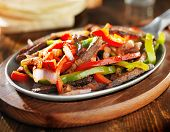 picture of mexican  - mexican beef fajitas in iron skillet with tortillas in background - JPG