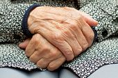 picture of retirement age  - An elderly woman touch her wrinkled hand - JPG