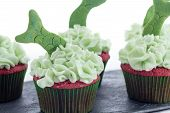 picture of shale  - Tasty cupcakes with green icing and fish tails decoration on a shale tray