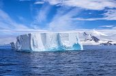 stock photo of iceberg  - Antarctic iceberg floating in the ocean with beautiful background. 