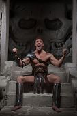picture of sparta  - Gladiator in armour sitting on steps of ancient temple celebrating victory - JPG