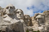 picture of mount rushmore national memorial  - view of Mount Rushmore National Monument on a spring morning with some clouds and sunshine - JPG