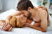 stock photo of intimacy  - Hands of female and male lying on bed and kissing - JPG