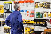 stock photo of hardware  - Rear view of worker with hands on hip standing in hardware store - JPG