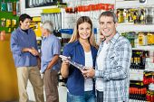 foto of hardware  - Portrait of happy couple buying tool set in hardware store with people hand shaking in background - JPG