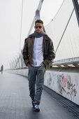 picture of jacket  - Handsome trendy young man standing on a sidewalk wearing a fashionable leather jacket and scarf in a relaxed confident pose looking at the camera - JPG