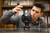 picture of seer  - Handsome young male soothsayer predicting the future by looking into black crystal ball - JPG