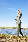 stock photo of fisherwomen  - woman fishing at a pond at spring country - JPG