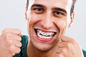 picture of braces  - Photo of young man with braces using dental floss - JPG