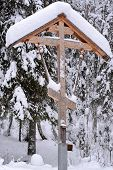 stock photo of baptism  - Orthodox antique handmade wooden cross in winter forest on baptism - JPG