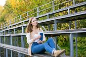 picture of tribunal  - Student sitting on sport tribune with book and smiling at camera