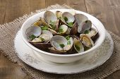 stock photo of clam  - cooked clams in wine sauce with spring onion in a bowl - JPG