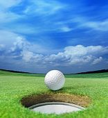 image of caddy  - golf ball on lip of cup of lovely beautiful golf course - JPG