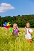 image of bubbles  - Two children in field playing with soap bubbles and windmill - JPG
