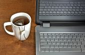 picture of hot-water-bag  - Tea bag in hot water with laptop on wood table - JPG