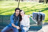stock photo of sticks  - Couple using a selfie stick in a park - JPG