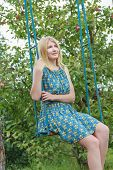 picture of swing  - Portrait of blonde girl in silk sundress is sitting on handmade swing