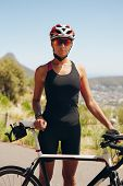picture of triathlon  - Portrait of confident female triathlete standing with her bicycle on country road - JPG