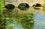 stock photo of old bridge  - Old stone bridge over river Coln in Village Bibury England UK - JPG