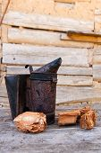 stock photo of beehive  - old smoker at beehive on the wooden table - JPG