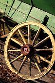 pic of olden days  - Rustic yellow wagon wheel on green cart - JPG