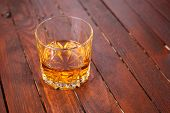 stock photo of tumblers  - Tumbler glass full of whisky standing on a wooden table - JPG