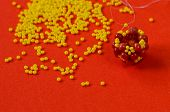 stock photo of beads  - Beads For A Unique Necklace. Wattled beaded bead on an orange background.