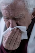 picture of blowing nose  - Elderly sick man blowing his rainy nose - JPG