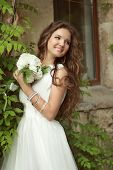 stock photo of wavy  - Outdoor Portrait Of Beautiful Happy Bride with long wavy hair in white wedding dress - JPG