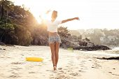 pic of beach sunset  - carefree woman dancing in the sunset on the beach - JPG